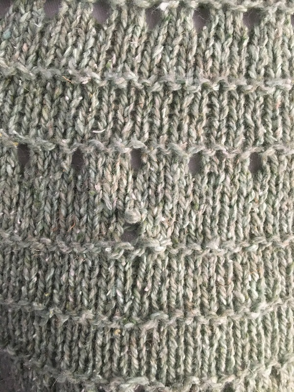Closeup of the dropped stitch in the Derecho knitted tee.  There is an easy way to fix a dropped stitch.